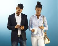 Young couple with mobilephone. Young couple using mobilephone over blue background Stock Images