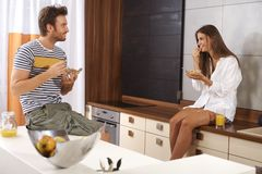 Young couple in the morning. Young loving couple having breakfast in the kitchen, smiling happy Royalty Free Stock Photos