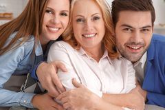 Young couple with mother-in-law at home weekend family portrait. Young couple man and woman with mother-in-law at home weekend looking camera hugging smiling Stock Images