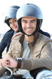 Young couple on motorbike. Young couple smiling sitting on motorbike with helmets Royalty Free Stock Image