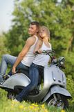 Young couple on motorbike / scooter on nature Royalty Free Stock Photos