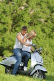 Young couple on motorbike / scooter on nature. Young happy couple on motorbike / scooter on natural background Royalty Free Stock Image