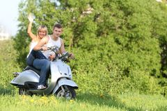 Young couple on motorbike / scooter on nature. Young happy couple on motorbike / scooter on natural background Royalty Free Stock Images