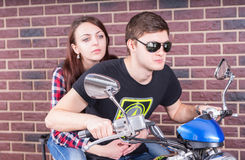 Young Couple on Motorcycle in front of Brick Wall. Young Man Wearing Sunglasses and Chewing on Toothpick Riding on Motorcycle in front of Brick Wall with Young Royalty Free Stock Image