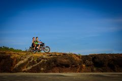 Young couple on a motorcycle on on rocky ground. Happy guy and girl travelling on a motorbike.  stock photography