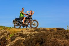 Young couple on a motorcycle on on rocky ground. Happy guy and girl travelling on a motorbike.  royalty free stock images