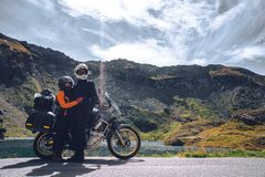 Young couple of motorcycle travelers in the autumn mountains of Romania. Moto tourism and moto travellers lifestyle while royalty free stock photography