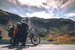 Young couple of motorcycle travelers in the autumn mountains of Romania. Moto tourism and moto travellers lifestyle while royalty free stock photos
