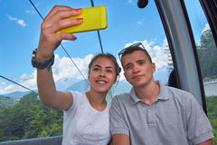 Young couple on mountain lift taking a selfie Royalty Free Stock Image