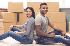 Young couple moving. Beautiful couple is looking at camera and smiling while sitting back to back in the room among moving boxes Royalty Free Stock Image