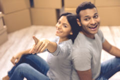 Young couple moving. Beautiful couple is looking at camera and smiling while sitting back to back in the room among moving boxes. Girl is pointing at camera Stock Photography