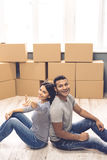 Young couple moving. Beautiful couple is looking at camera and smiling while sitting back to back in the room among moving boxes. Girl is pointing at camera Stock Photos
