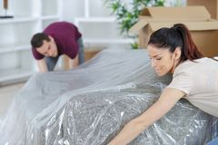 Young couple moving couch to their new apartment royalty free stock photo