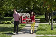Young couple moving a dollhouse Royalty Free Stock Photo