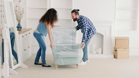 Young couple moving furniture new apartment