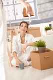 Young couple moving home woman sitting with boxes. Young couple moving home, woman sitting on floor with boxes around, man hanging keys front of her Stock Photography