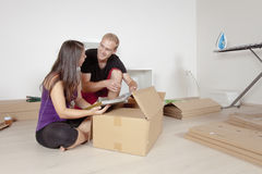 Young Couple Moving, Looking at Old Pictures Stock Image