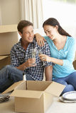 Young Couple Moving Into New Home Celebrating With Champagne Stock Image