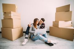 Young couple moving in a new home. Man and woman with notebook laptop computer and boxes in empty room. stock photography