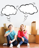 Young couple moving in a new home. Man and woman unboxing fragil Royalty Free Stock Photography