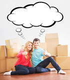 Young couple moving in a new home. Man and woman unboxing fragil Stock Images