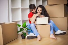 Young couple moving in new home.Sitting and relaxing after unpacking.Looking something on laptop. Young couple royalty free stock photo