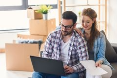 Young couple moving in new home. Sitting and relaxing after unpacking. Searching for ideas on laptop. royalty free stock photos