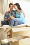 Young Couple Moving Into New Home Surrounded By Packing Boxes Royalty Free Stock Photos
