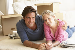 Young Couple Moving Into New Home Surrounded By Packing Boxes Royalty Free Stock Images