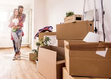 Young couple moving in new home. Unpacking box containers and cleaning. stock image