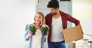 Young couple Moving in new home and unpacking carboard boxes. Young married couple Moving in new home and unpacking carboard boxes Stock Photo