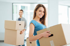 Young couple moving in a new house. Happy smiling couple moving in a new house and carrying carton boxes, relocation and renovation concept stock photo