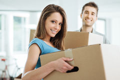 Young couple moving in a new house. Happy smiling couple moving in a new house and carrying carton boxes, relocation and renovation concept royalty free stock photo