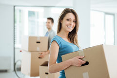 Young couple moving in a new house. Happy smiling couple moving in a new house and carrying carton boxes, relocation and renovation concept stock photos