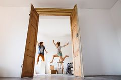 Young couple moving in a new house, jumping up high. Stock Images