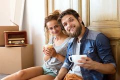 Young couple moving in new house, resting. Royalty Free Stock Photos