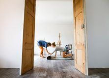 Young couple moving in new house, rolling out carpet. Stock Images