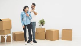 Young couple is moving to a new apartment together. Smiling couple. Surprised girl. Hugging. Close up. Copy space. 4K. Concept relocation. Perfect match stock video footage