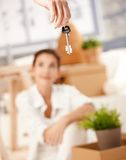 Young couple moving to new house keys hanging. Young woman sitting on floor, man hanging keys of new house in foreground Stock Photography
