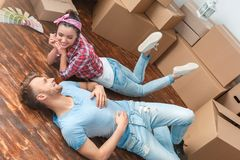 Young couple moving to new place lying talking smiling happy. Young husband and wife moving to new place lying on floor talking relaxed looking at each other royalty free stock images