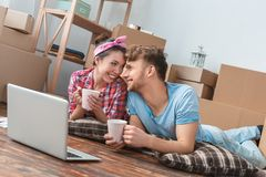 Young couple moving to new place lying using laptop holding cups with tea looking at each other playful closeness. Young husband and wife moving to new place stock images