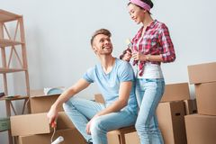 Young couple moving to new place man with paint roller sitting on box laughing looking at woman standing with brush royalty free stock image