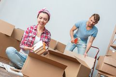 Young couple moving to new place packing woman putting books into box dreamful while man taping happy royalty free stock image