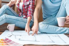 Young couple moving to new place sitting drinking coffee pointing together at house draft close-up royalty free stock image