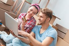 Young couple moving to new place sitting drinking tea doing online shopping on laptop joyful royalty free stock images