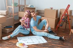 Young couple moving to new place sitting drinking tea dreamful royalty free stock photos