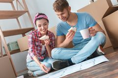 Young couple moving to new place sitting eating sandwiches drinking coffee looking at plan happy stock photo