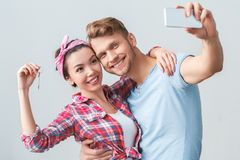 Young couple moving to new place standing hugging holding key taking selfie photos with smartphone joyful stock images