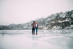 Young couple with mug of tea walks on ice of frozen lake. Young couple with mug of tea walks on ice of frozen lake against rocks background royalty free stock photography