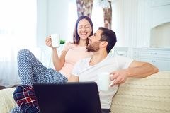 A young couple with a laptop in their hands are laughing in the royalty free stock images